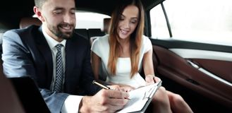 Beautiful business woman working with a client in the car. Handsome businessman in suit  is using a laptop and studying documents while driving on back seat in Royalty Free Stock Images
