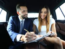 Beautiful business woman working with a client in the car. Handsome businessman in suit  is using a laptop and studying documents while driving on back seat in Stock Photo