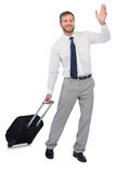 Handsome businessman with suitcase waving Stock Photos