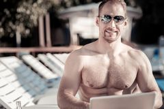 Handsome businessman in sunglasses beaming while working outdoors stock photos