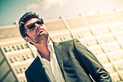 Handsome businessman with sunglasses. Outdoor in the city. Charming and modern style, with shirt and suite. Cool hairstyle. Behind him a high-rise office Royalty Free Stock Images