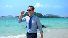 Handsome businessman in sunglasses walked along a tropical beach, taking off his tie royalty free stock photo