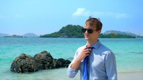 Handsome businessman in sunglasses walked along a tropical beach, taking off his tie royalty free stock image