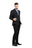 Handsome businessman taking cellphone from his pocket side view. Full body length portrait isolated over white studio background Royalty Free Stock Images