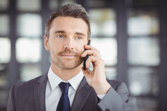 Handsome businessman talking on cellphone Stock Photos
