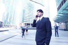 Businessman talking on cellphone. Handsome businessman talking on the cellphone outside office building Stock Image