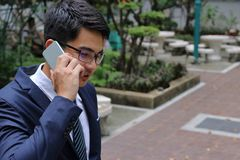 Handsome businessman talking on his mobile phone in city park. Stock Images
