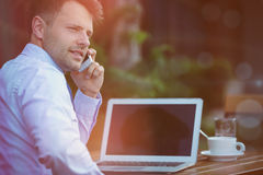 Handsome businessman talking on mobile phone while sitting by laptop Stock Photos