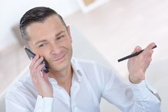 Handsome businessman talking on mobile phone and smiling Royalty Free Stock Photos