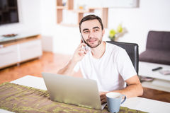 Handsome businessman is talking on the mobile phone and smiling while using a laptop in kitchen Royalty Free Stock Photography