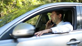 Handsome businessman talking on phone in car stock footage
