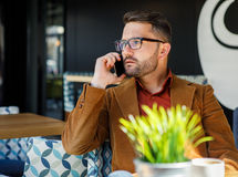 Handsome businessman talking on the phone in coffee shop Stock Images