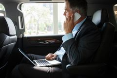 Handsome businessman talking with phone sitting with laptop on the backseat of the car. Royalty Free Stock Images