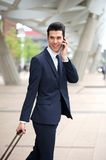 Handsome businessman talking on phone and walking outdoors Royalty Free Stock Photography