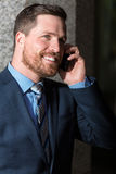 Handsome businessman talking on the phone. Handsome young  businessman with beard and blue eyes talking on the phone Royalty Free Stock Photo
