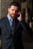 Handsome businessman talking on the phone. Handsome young  businessman with beard and blue eyes talking on the phone and posing for the camera Royalty Free Stock Photos
