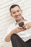 Handsome businessman texting on mobilephone Stock Photos