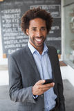 Handsome businessman texting on phone Royalty Free Stock Photography