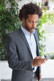 Handsome businessman texting on phone Royalty Free Stock Images