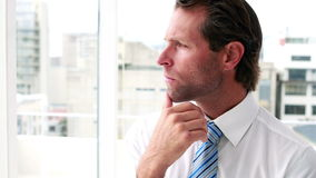 Handsome businessman thinking and looking out window stock video