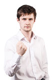 Handsome businessman threaten by fist. Young handsome businessman shows threaten fist isolated on white stock photography