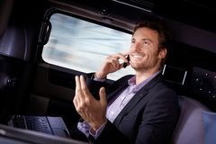 Handsome businessman traveling in limousine. Handsome young businessman traveling in limousine, working on laptop computer, talking on mobile phone, smiling Stock Images