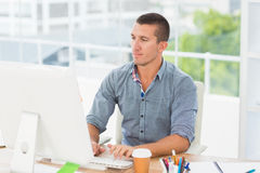 Handsome businessman typing on a computer Stock Images