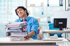 The handsome businessman unhappy with excessive work in the office. Handsome businessman unhappy with excessive work in the office royalty free stock photo