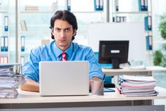 The handsome businessman unhappy with excessive work in the office. Handsome businessman unhappy with excessive work in the office stock image