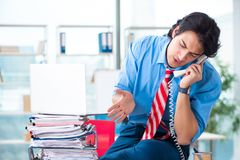 The handsome businessman unhappy with excessive work in the office. Handsome businessman unhappy with excessive work in the office royalty free stock photos