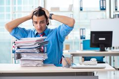 The handsome businessman unhappy with excessive work in the office. Handsome businessman unhappy with excessive work in the office royalty free stock images