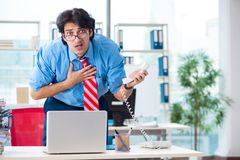 The handsome businessman unhappy with excessive work in the office. Handsome businessman unhappy with excessive work in the office stock images