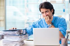 The handsome businessman unhappy with excessive work in the office. Handsome businessman unhappy with excessive work in the office royalty free stock photography