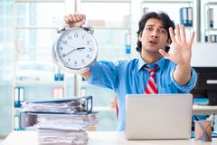 The handsome businessman unhappy with excessive work in the office. Handsome businessman unhappy with excessive work in the office royalty free stock image