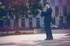 Handsome businessman using digital tablet on road against office Stock Photography