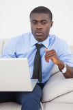 Handsome businessman using laptop on sofa Stock Images