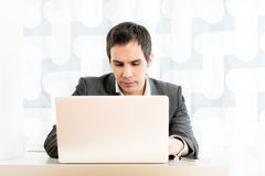 Handsome Businessman Using Laptop on the Table Stock Photography