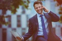 Handsome businessman using mobile phone and digital tablet Royalty Free Stock Photography