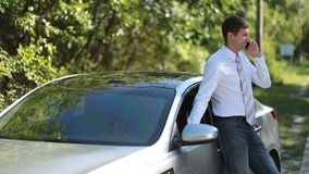 Handsome businessman using mobile phone near car stock footage