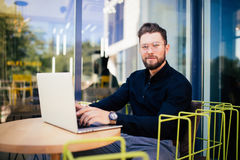 Handsome businessman using modern laptop outdoors, successful manager working in cafe during break and searching information in in. Handsome businessman using Stock Photos