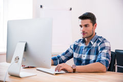 Handsome businessman using PC at the table stock photography