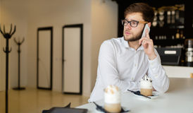 Handsome businessman using phone and wearing glasses Royalty Free Stock Photography