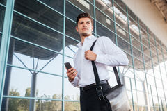 Handsome businessman using smartphone near office building. Handsome young businessman using smartphone outdoors near office building Royalty Free Stock Images