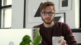 Handsome businessman is using a smartphone and smiling while working in office 20s 4k.  stock video