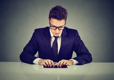 Handsome businessman using a tablet computer while working at desk stock photo