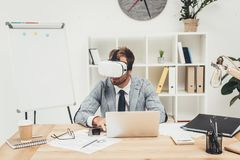 Handsome businessman in vr headset sitting. In office Stock Photo