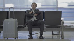 Businessman in the waiting hall in the airport. Handsome businessman waits for boarding at the airport waiting hall. Attractive man impatiently looks at his stock footage