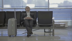 Businessman in the airport waiting walks to the gate. Handsome businessman waits for boarding at the airport waiting hall. Attractive man opens his eyes and stock video
