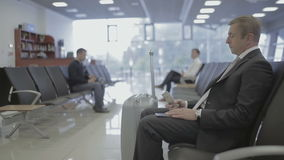 Handsome businessman waits for boarding at the airport waiting hall. Businessman looks at his phone. Attractive man looks at his wrist watch, takes his stock footage