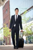 Handsome businessman walking outdoors with bag Royalty Free Stock Photography